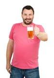 Hombre sonriente que lleva a cabo la pinta de la cerveza dorada Fotos de archivo