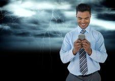 Hombre sonriente que manda un SMS en oscuridad con lightenings imagen de archivo libre de regalías