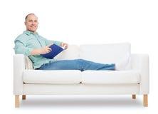 Hombre sonriente que miente en el sofá con el libro Fotos de archivo libres de regalías