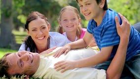 Hombre sonriente que miente en la hierba con su familia almacen de video
