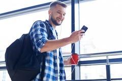Hombre sonriente que mira el teléfono Imágenes de archivo libres de regalías