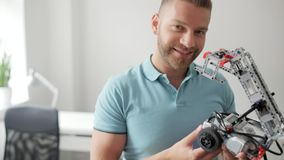 Hombre sonriente que muestra su máquina robótica en cámara