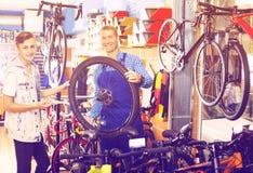 Hombre sonriente que repara la rueda y la charla de la bici Imágenes de archivo libres de regalías