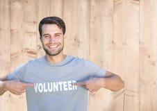 Hombre sonriente que señala en el título voluntario en su camiseta Fotografía de archivo libre de regalías