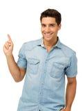 Hombre sonriente que señala para arriba contra el fondo blanco Imagen de archivo libre de regalías