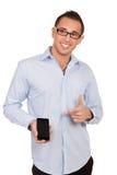 Hombre sonriente que señala a su móvil Fotografía de archivo libre de regalías