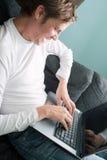 Hombre sonriente que se divierte en el ordenador portátil Foto de archivo
