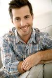 Hombre sonriente que se relaja en casa Fotos de archivo