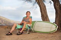 Hombre sonriente que se sienta con la tabla hawaiana Imágenes de archivo libres de regalías