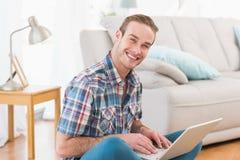 Hombre sonriente que se sienta en el piso usando el ordenador portátil Imagen de archivo libre de regalías