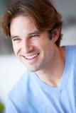 Hombre sonriente que se sienta en el sofá foto de archivo libre de regalías