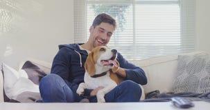 Hombre sonriente que se sienta en el sofá que frota ligeramente su perro casero mientras que mira la televisión 4K 4k metrajes