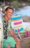 Hombre sonriente que se sienta en la playa Fotos de archivo libres de regalías