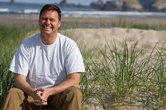 Hombre sonriente que se sienta en la playa Foto de archivo libre de regalías