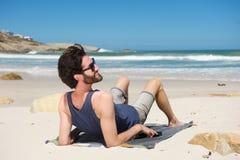 Hombre sonriente que se sienta en la playa aislada Fotos de archivo libres de regalías