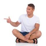 Hombre sonriente que se sienta en piso y señalar Imagen de archivo