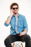 Hombre sonriente que se sienta en silla y que habla por el teléfono celular Foto de archivo libre de regalías