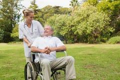 Hombre sonriente que se sienta en una silla de ruedas que habla con su pushi de la enfermera Imágenes de archivo libres de regalías
