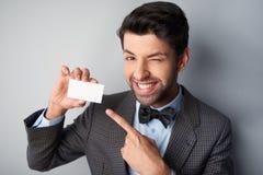 Hombre sonriente que señala en la tarjeta de visita en blanco y Imagen de archivo libre de regalías