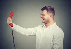 Hombre sonriente que sostiene el receptor rojo del teléfono imagenes de archivo