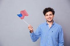 Hombre sonriente que sostiene la bandera de los E.E.U.U. Fotografía de archivo