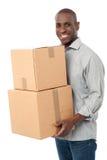 Hombre sonriente que sostiene las cajas de cartón Imagen de archivo