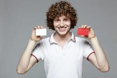 Hombre sonriente que sostiene tarjetas del crédito en blanco Imagen de archivo libre de regalías