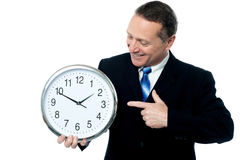 Hombre sonriente que sostiene un reloj en sus manos Imagenes de archivo