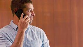 Hombre sonriente que tiene una llamada de teléfono metrajes