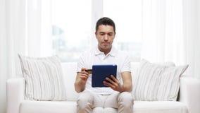 Hombre sonriente que trabaja con PC de la tableta en casa metrajes