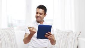 Hombre sonriente que trabaja con PC de la tableta en casa almacen de metraje de vídeo