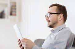 Hombre sonriente que trabaja con PC de la tableta en casa Imagen de archivo