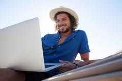 Hombre sonriente que usa el ordenador portátil mientras que se relaja en la hamaca en la playa Fotografía de archivo libre de regalías