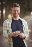 Hombre sonriente que usa el teléfono móvil en la granja verde oliva Imagenes de archivo