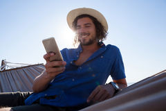 Hombre sonriente que usa el teléfono móvil mientras que se relaja en la hamaca en la playa Fotografía de archivo libre de regalías