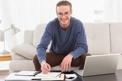 Hombre sonriente que usa la calculadora que cuenta sus cuentas Imagen de archivo libre de regalías