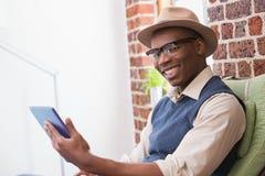 Hombre sonriente que usa la tableta de Digitaces Imagenes de archivo