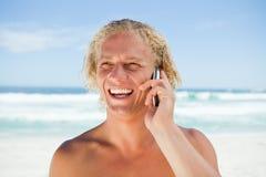 Hombre sonriente que usa su teléfono móvil mientras que se coloca en la playa Foto de archivo