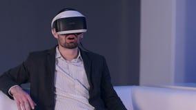 Hombre sonriente relajado en traje que goza del simulador de la realidad virtual Foto de archivo