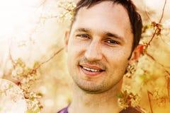 Hombre sonriente y un árbol floreciente Foto de archivo libre de regalías