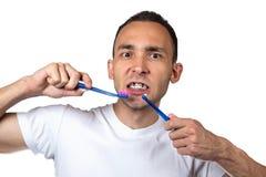 Hombre, soportes y cepillo de dientes desconcertados Fotografía de archivo