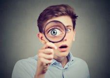 Hombre sorprendente curioso que mira a través de una lupa Imagen de archivo libre de regalías