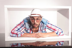 Hombre sorprendente de la moda de los jóvenes que miente dentro de una caja blanca Imagen de archivo libre de regalías