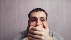 Hombre sorprendente que cubre su boca sobre fondo de la pared almacen de metraje de vídeo