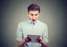 Hombre sorprendente que mira su nueva tableta Foto de archivo libre de regalías