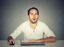 Hombre sorprendente que usa el ordenador en el escritorio foto de archivo libre de regalías