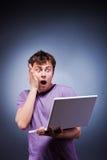 Hombre sorprendido con la computadora portátil Foto de archivo