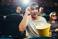 Hombre sorprendido con la película de observación de las palomitas en cine Fotos de archivo libres de regalías