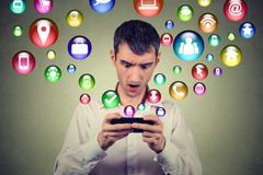 Hombre sorprendido que usa iconos sociales de los símbolos del uso del smartphone los medios que vuelan de la pantalla Imagenes de archivo