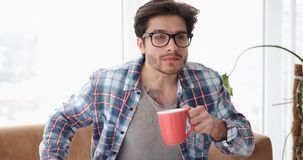 Hombre sorprendido que ve la TV mientras que bebe el café almacen de video